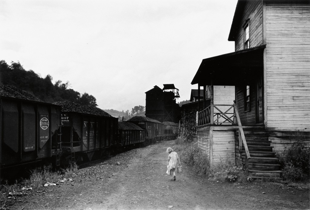 "Image via Swann Galleries. ""Coal Miner's Child Carrying Home Can of Kerosene, Company houses, Scotts Run, W. Va.,"" 1938; printed 1977. Marion Post Wolcott."