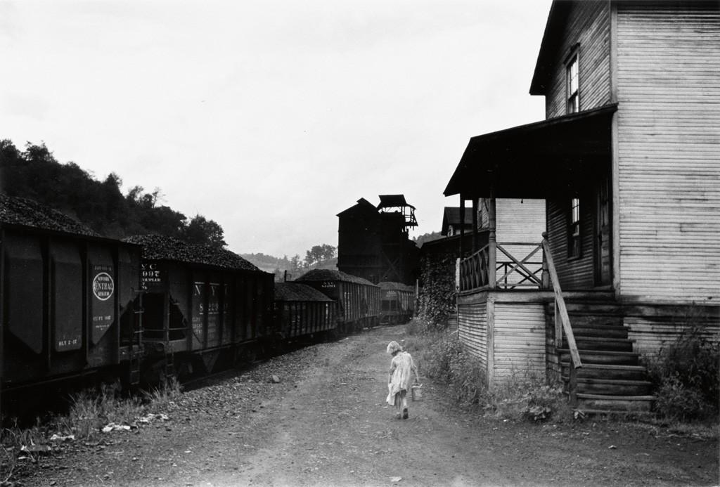 "Image via Swann Galleries. ""Coal Miner's Child Carrying Home Can of Kerosene, Company houses, Scotts Run, W. Va.,"" 1938; printed 1977. Marion Post Wolcott."