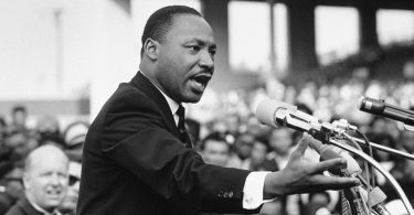 Martin Luther King, Jr. giving a speech at a podium, black and white photo