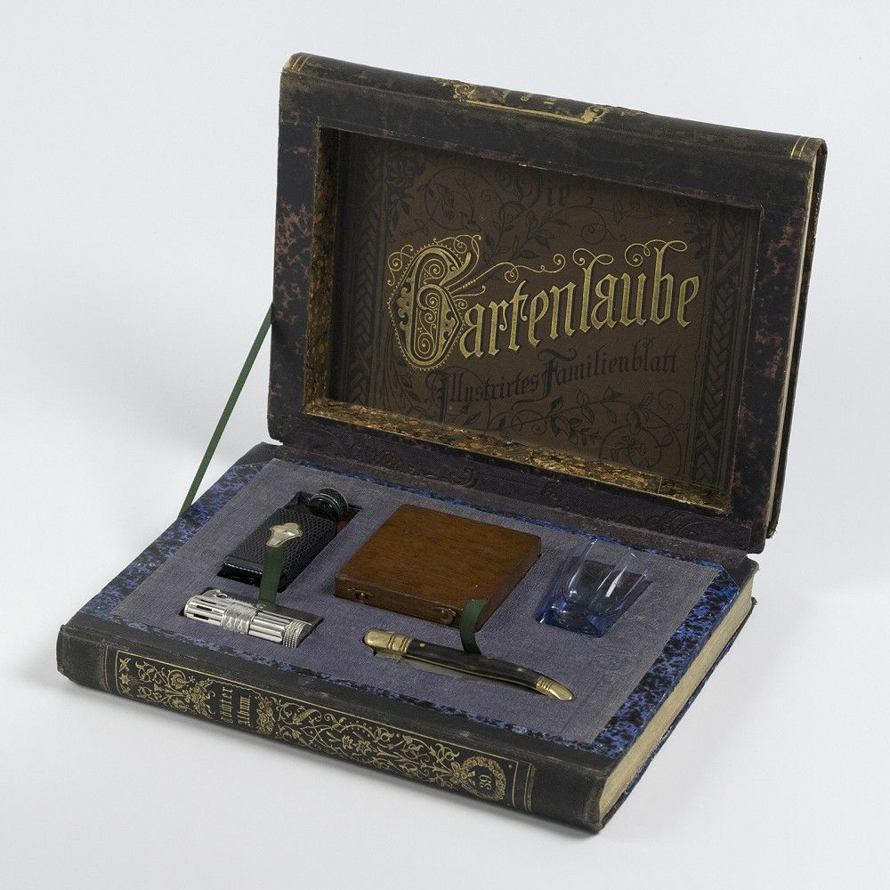 Image of book that opens to reveal a hidden compartment with shot glass, penknife, jagermeister, and other handy tools.