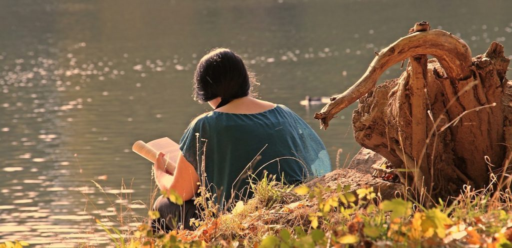 A woman sits reading alone on the banks of a river with autumn leaves on the ground. Her back is to the camera.